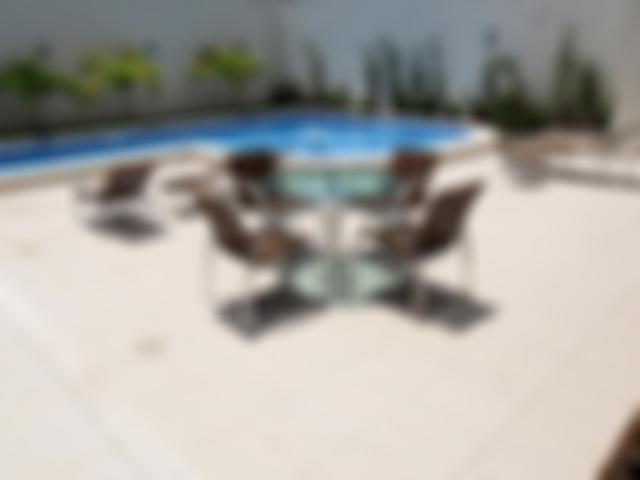 Area da piscina com espaço para banho de sol